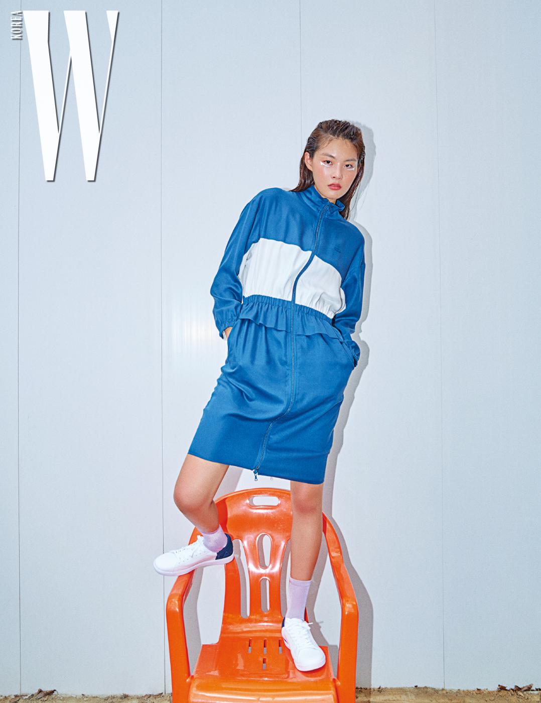 흰색과 파란색의 대비가 경쾌한 느낌을 주는 트랙 재킷 스타일의 원피스, 네이비색 힐 부분이 특징인 하얀 스니커즈는 모두 Lacoste 제품.