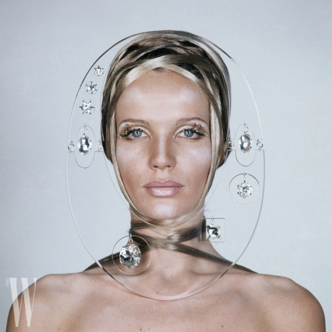Beauty shot of Veruschka wrapped in strands of her own hair, with shiny stones glued to her eyelashes, and her face framed by clear plexiglass with hanging crystals *** Local Caption *** Veruschka;
