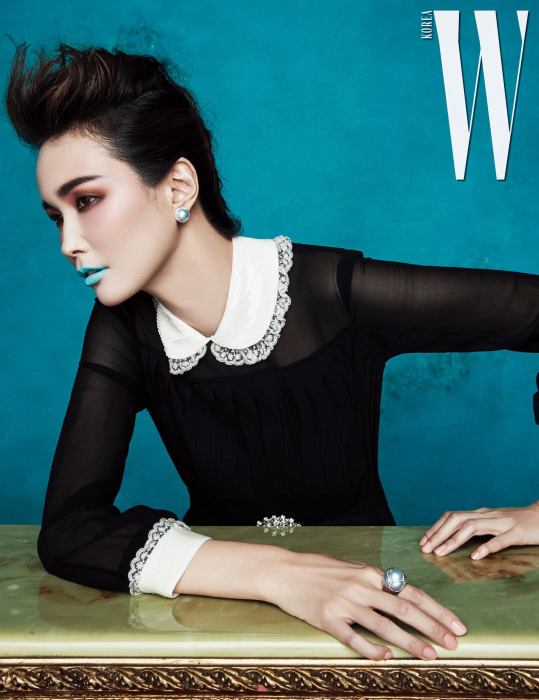 리츠 파리 스위트의 오브제에서  영감 받은 것으로 섬세한 광채의  마베 진주와 다이아몬드가 어우러진  화이트 골드 소재의 귀고리와  반지는 Tasaki 제품.  레이스 장식의 칼라와 소매가  여성스러운 드레스와  주얼 벨트는 Miu Miu 제품.
