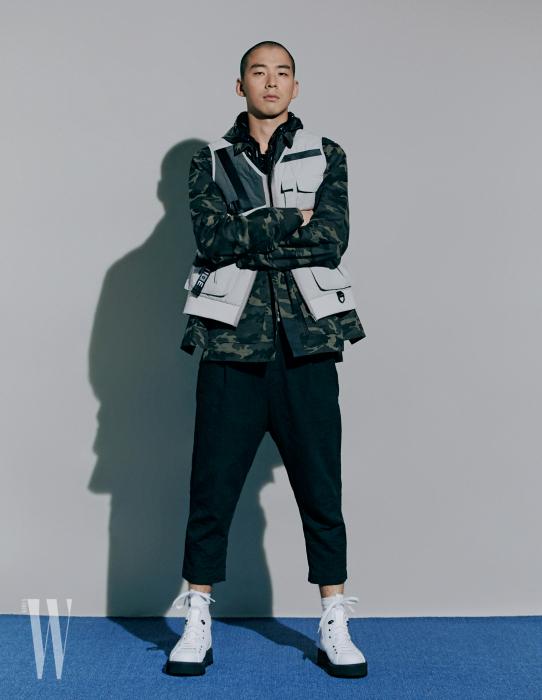 한국 군복에서 영감 받은 밀리터리 재킷, 멀티 포켓 베스트, 광택 있는 후디 집업, 팬츠는 모두 이세, 부츠는 지제냐 제품.