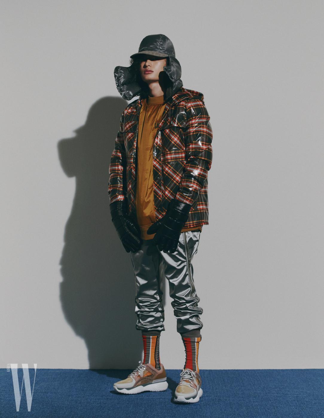 비닐이 코팅된 체크 재킷, 삭스는 보테가 베네타, 오렌지색 다운 톱은 준지, 은색 지퍼 장식 팬츠는 루이 비통, 모자와 장갑은 지제냐, 핑크색 스니커즈는 펜디 제품.