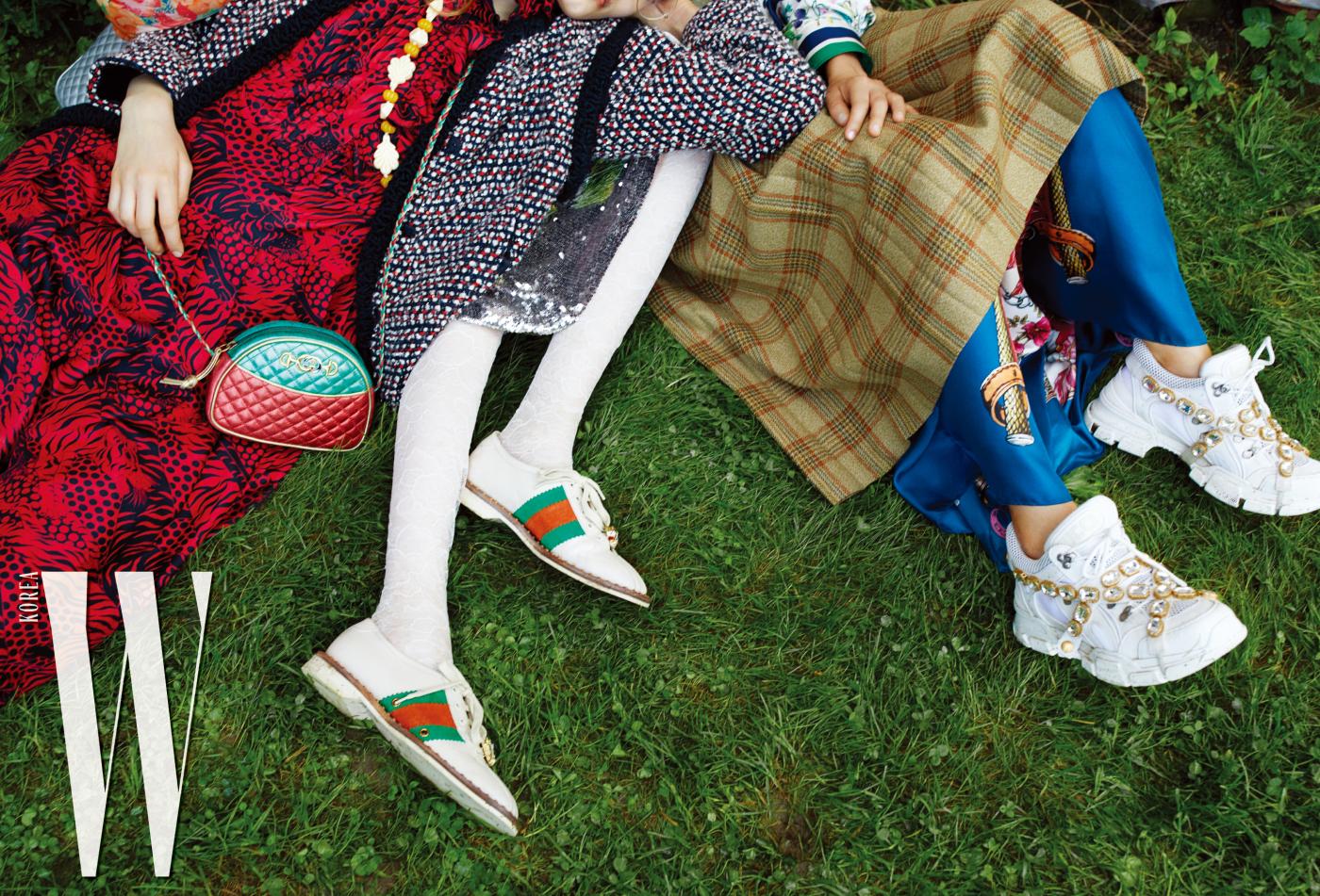 리나가 착용한 트위드 재킷, 레드-블랙 타이거 프린트의 실크 플리츠 드레스, 원석 목걸이, 홀스빗이 더해진 G 디테일의 메탈릭 마틀라세 가죽 숄더백, 케이가 착용한 화려한 프린트의 패딩 재킷, 시퀸 스커트, 흰색의 플로럴 레이스 타이츠, 웹 디테일이 돋보이는 스웨이드 소재 레이스업 스니커즈, 사라가 착용한 그린 로즈 페스티벌 프린트의 셔츠, 슈가케인 헌팅 체크 스커트, 트윌 프린트 롱 스커트, 크리스털 스트랩과 SEGA 그래픽 폰트의 구찌 로고 디테일이 특징인 흰색의 레이스업 스니커즈는 모두 Gucci 제품.