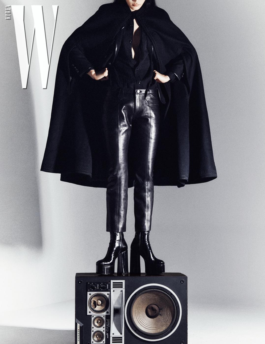 드라마틱한 실루엣을 연출하는 울 소재 케이프, 울 개버딘 블레이즈, 실크 셔츠, 가죽 팬츠, 빌리 버클 부츠는 모두 Saint Laurent by Anthony Vaccarello 제품.