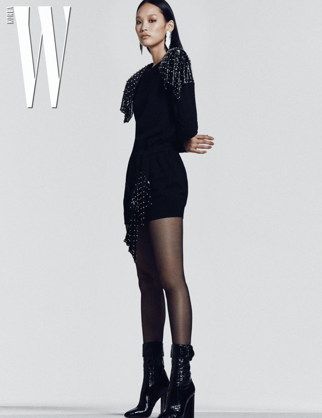 메탈 스터드 장식의 벨티드 미니드레스, 클립형 크리스털 이어링, 조플린 버클 부츠는 모두 Saint Laurent by Anthony Vaccarello 제품.