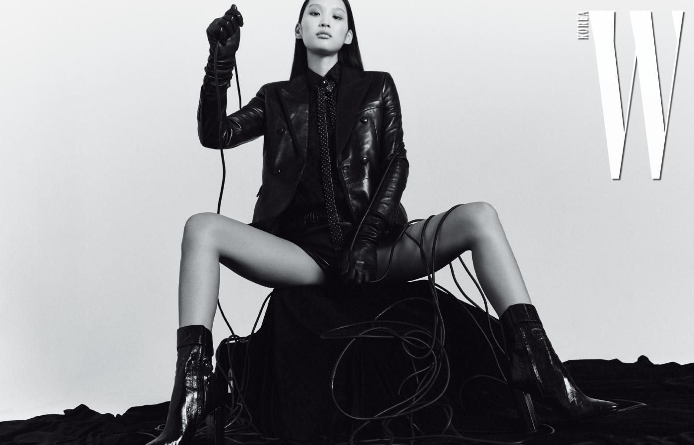 가죽 테일러 파이핑 재킷, 검정 파리 컬렉션 셔츠, 미니 쇼츠, 스터드 장식 타이, 롱 레더 글러브, 조플린 버클 부츠, 블랙 페이턴트 가죽 라지 비키 백은 모두 Saint Laurent by Anthony Vaccarello 제품.