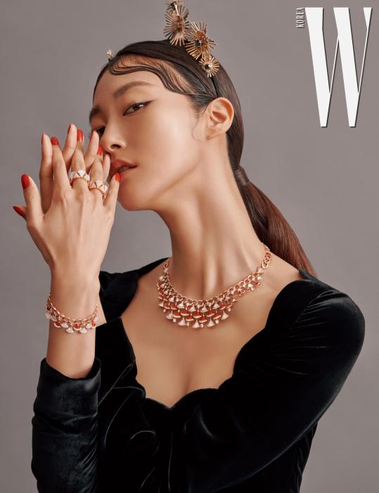 디바스 드림 하이 주얼리 컬렉션의 붉고 탐스러운 커넬리안과 마더오브펄, 다이아몬드가 세팅된 로즈 골드 목걸이와 팔찌, 다이아몬드 혹은 마더오브펄과 다이아몬드가 세팅된 로즈 골드 반지는 모두 Bulgari 제품. 조형적인 메탈 장식의  헤드피스는 Q Millinery,  유선형의 네크라인이 돋보이는 벨벳 드레스는 Valentino 제품