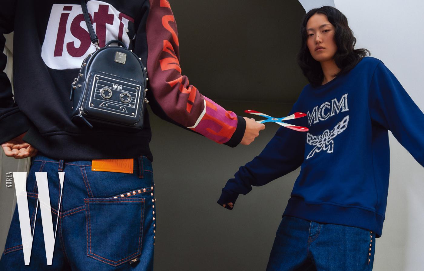 주노가 입은 후디 집업과 스터드 장식 데님 팬츠, 카세트 모양의 백팩, 이혜승이 입은 로고 스웨트셔츠와 데님 팬츠는 모두 MCM 제품.
