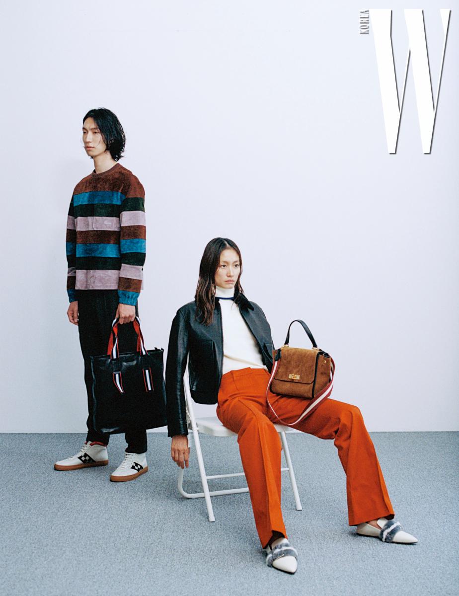 테이가 입은 줄무늬 스웨이드 톱과 검정 팬츠, 줄무늬 스트랩이 달린 '모린즈' 백과 큐브 무늬가 세련된 '비타파커' 스니커즈, 스웨터와 팬츠 모두 Bally 제품. 박세라가 입은 가죽 재킷과 흰색 터틀넥, 주홍색 바지, '하멜리아' 플랫 슈즈, '브리즈' 스몰 토트백은 모두 Bally 제품.