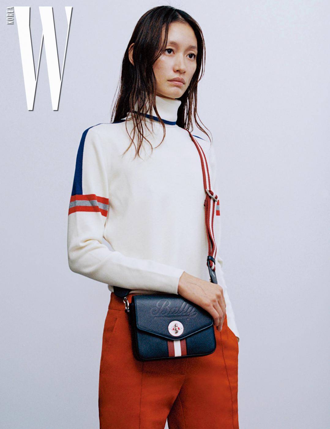 박세라가 든 음각 처리한 로고와 줄무늬가 클래식한 '타시아' 백, 의상은 모두 Bally 제품.