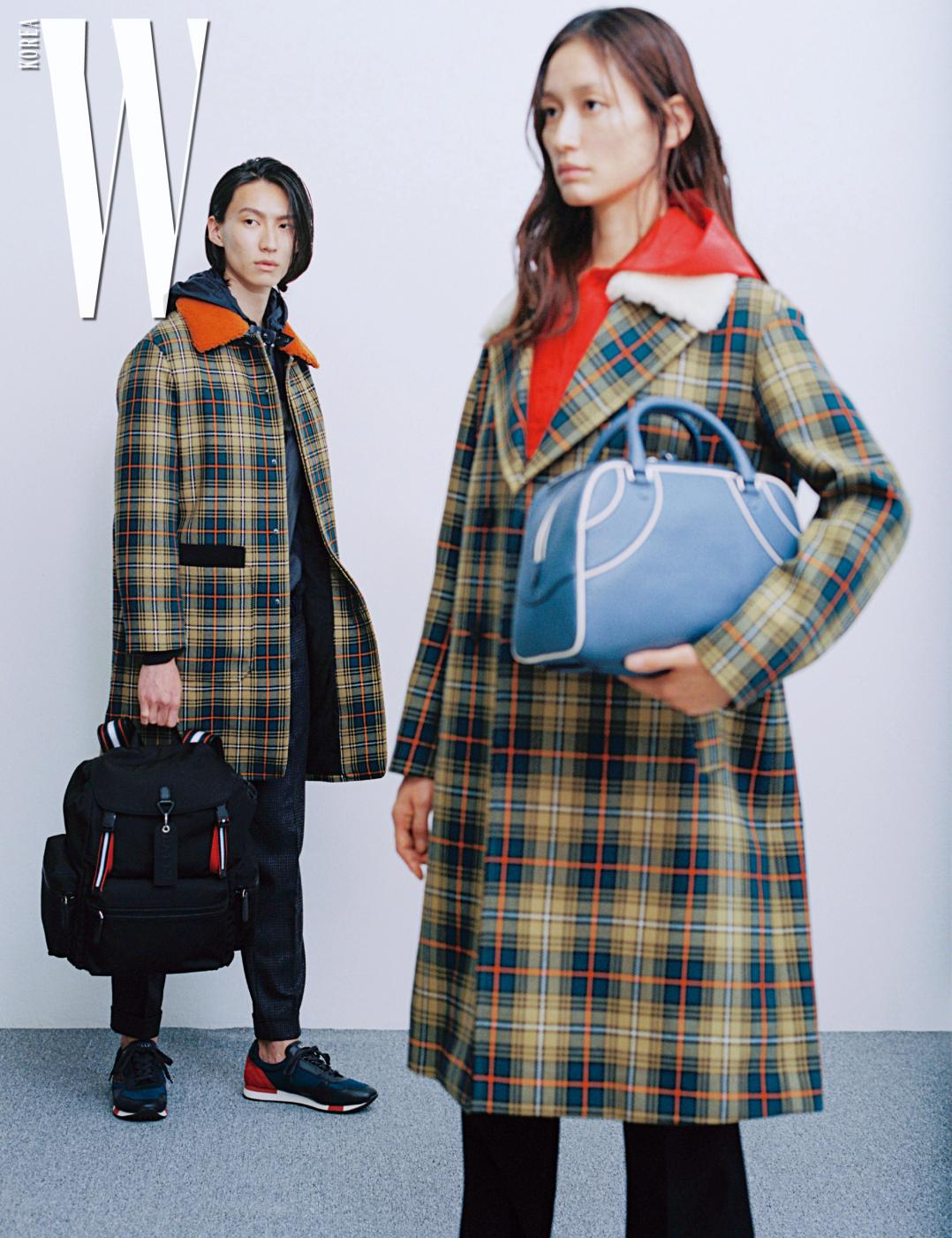 테이가 입은 체크무늬 코트와 가죽 재킷, 검은색 바지, 손에 든 '크루' 백팩, 뒤축에 붉은색 포인트가 있는 '가비노' 스니커즈는 모두 Bally 제품. 박세라가 입은 체크무늬 울 코트와 후드 점퍼, 손에 든 '달린 미듐' 백은 모두 Bally 제품.