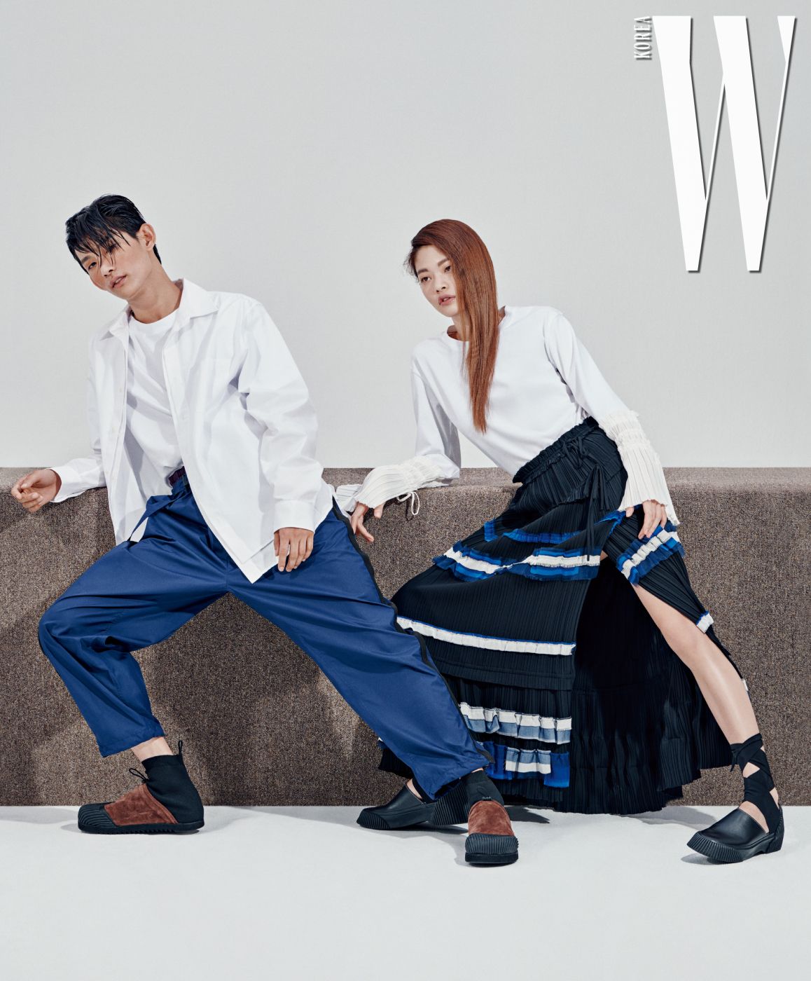 박형섭이 입은 흰색 레이어드 셔츠와 티셔츠, 더블 트랙 팬츠, 슈즈는 모두 3.1 Phillip Lim 제품. 김아현이 입은 플리츠 장식 톱, 티어드주름 스커트, 슈즈는 모두 3.1 Phillip Lim 제품.