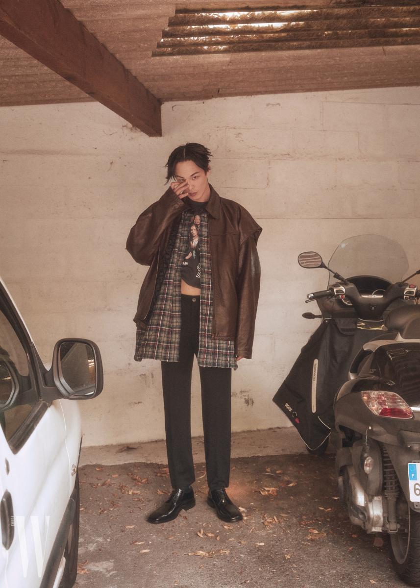 체크무늬 셔츠가 장식된 가죽 재킷, 티셔츠, 팬츠, 슈즈는 모두 Balenciaga 제품.