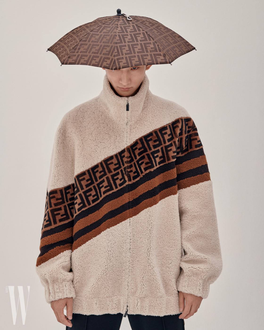 FF 로고의 우산 헤드피스와 시어링 집업 재킷, 팬츠는 펜디 제품.