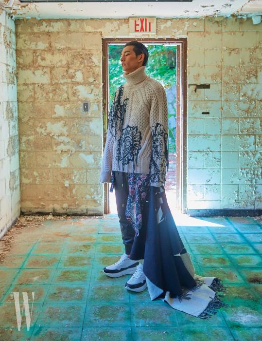 검은색 실장식 터틀넥과 가죽 팬츠, 스니커즈는 모두 Alexander McQueen, 허리에 두른 꽃무늬 셔츠는 H&M, 손에 든 로고 숄은 Valentino Garavani 제품.