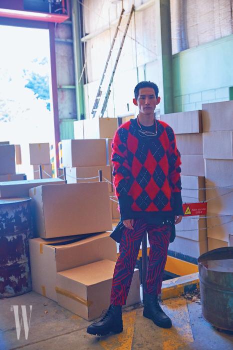 아가일 패턴 니트 톱은 Alexander McQueen, 패턴 팬츠는 Ports V, 검은색 비쿠나 라이닝 레이스업 부츠는 Ermenegildo Zegna Couture, 목에 건 선글라스는 Louis Vuitton 제품.
