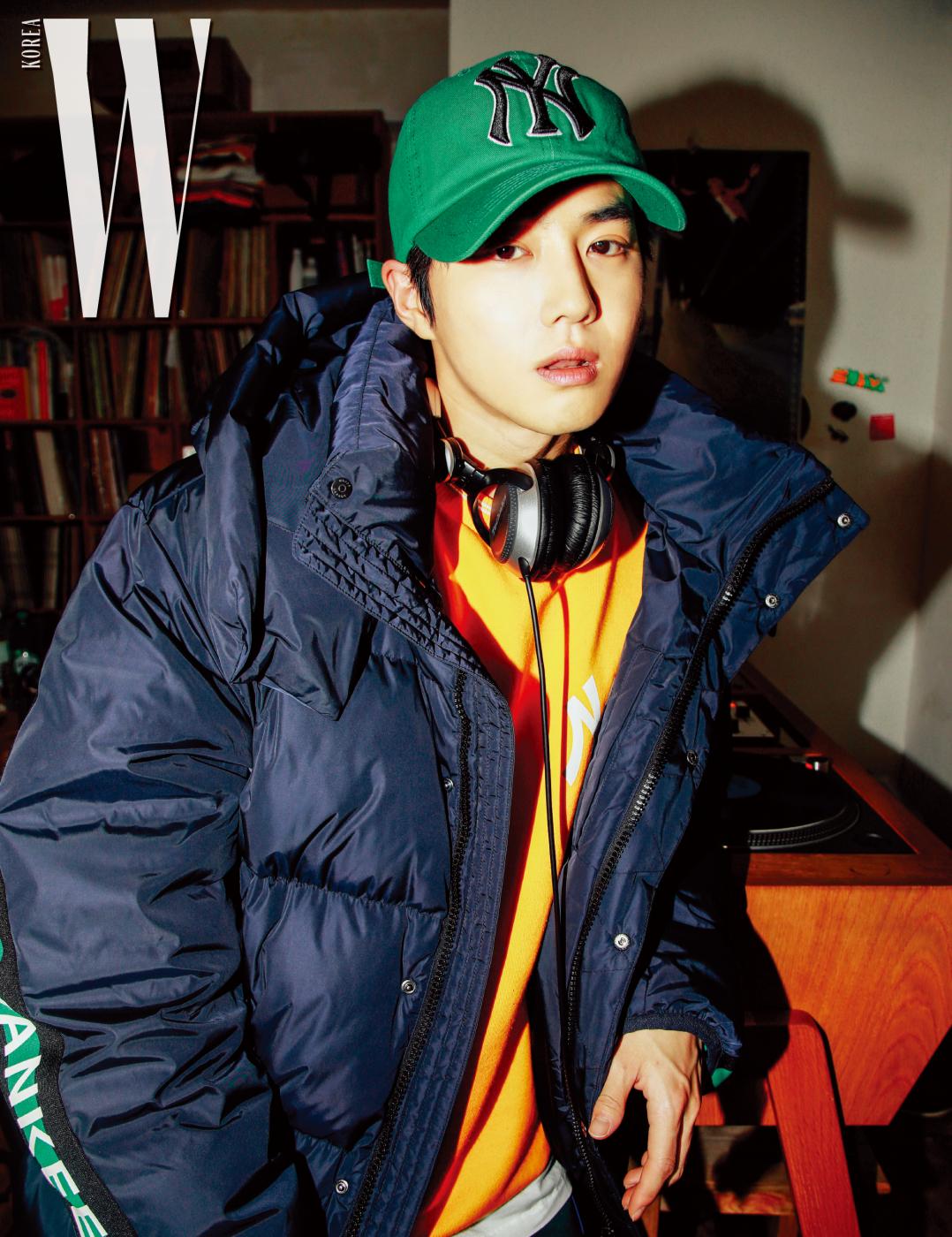 수호가 입은 레터링 테이프 장식 오리털 점퍼, 안에 입은 오렌지색 맨투맨, 초록색 메가로고 볼캡은 모두 MLB 제품.