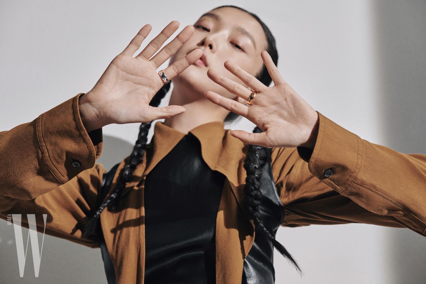 화이트 골드 소재의 스몰 코코 크러쉬 링과 옐로 골드 소재의 스몰 코코 크러쉬 링은 Chanel Fine Jewelry 제품. 길게 늘어진 칼라가 특징인 셔츠 드레스는 Vivienne Westwood, 가죽 베스트는 Zara 제품.