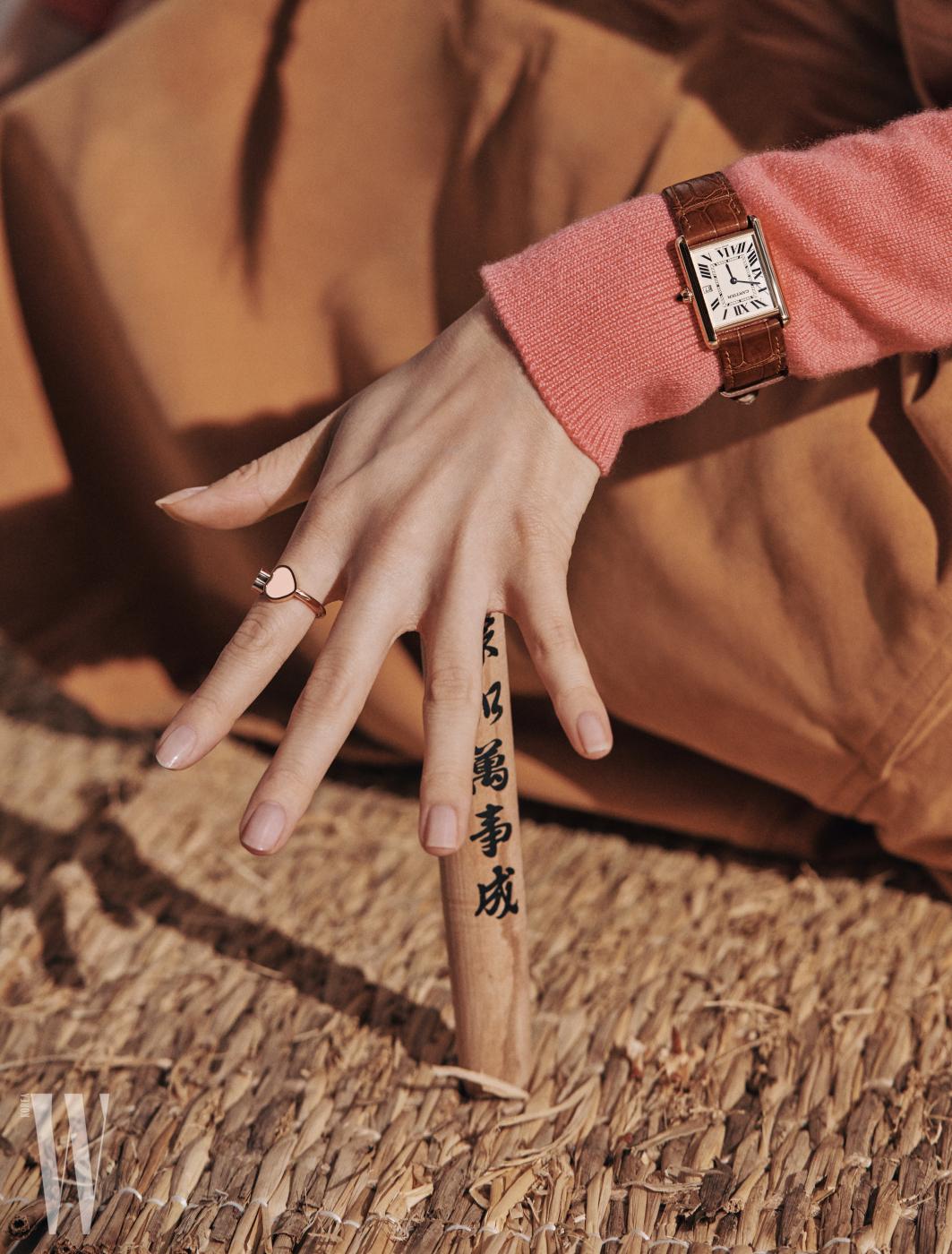 사랑스러운 하트 해피 H 링은 Chopard, 사파이어 카보숑을 세팅한 라지 사이즈 탱크 루이 까르띠에 워치는 Cartier 제품. 핑크색 카디건은 Chanel, 겨자색 스커트는 Acne Studios 제품.