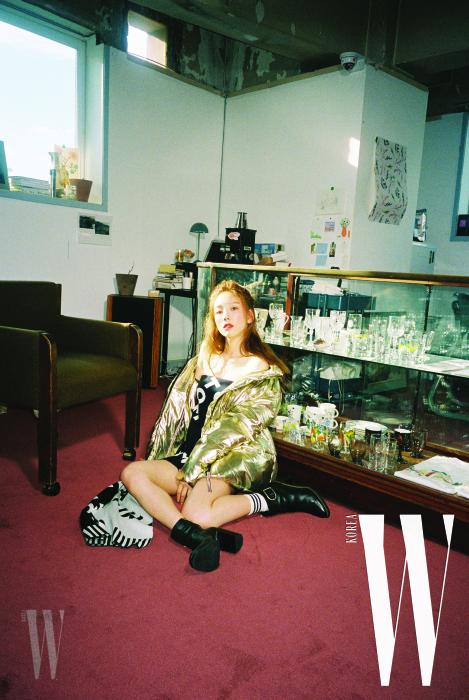 골드 패딩 점퍼는 Tommy Icons 제품. 드레스로 연출한 로고 머플러, 줄무늬 삭스, 버클 장식 앵클부츠는 모두 Tommy Hilfiger 제품.