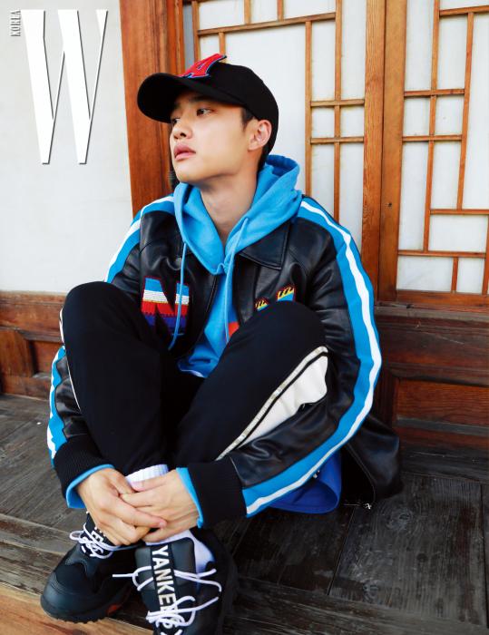 디오가 입은 에스닉한 무드의 로고 장식 양가죽 재킷, 안에 입은 하늘색 후디, 옆면의 라인이 돋보이는 검정 조거 팬츠, 글러브를 모티프로 한 스니커즈, 큼직한 로고 장식이 포인트인 메가로고 캡은 모두 MLB 제품.