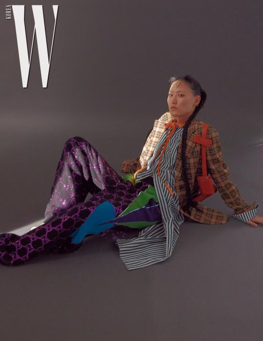줄무늬 셔츠 드레스는 Marni, 체크무늬 재킷은 Dries Van Noten, 스팽글 장식의 니트 팬츠는 Gucci, 어깨에 걸친 포켓 장식의 오렌지색 가죽 벨트는 Tod's 제품.