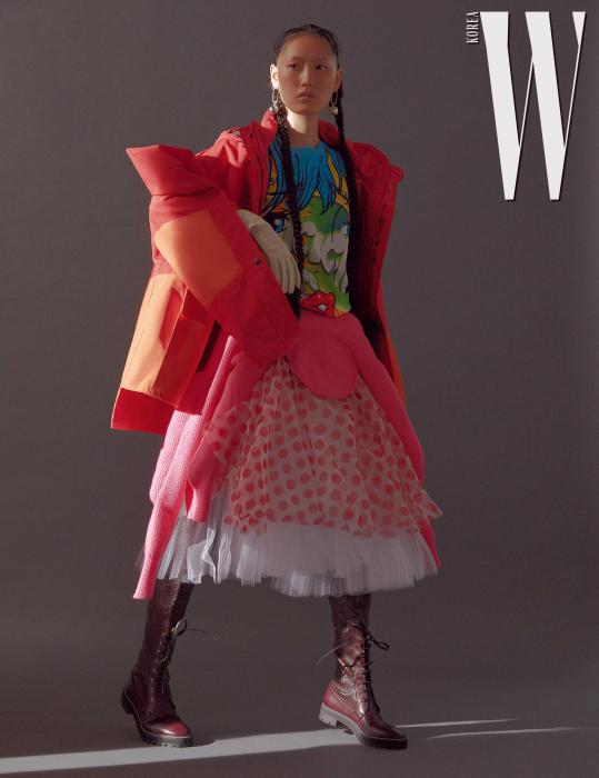 카툰 프린트의 티셔츠는 Moschino, 도트 패턴의 튤 장식 스커트와 분홍색 니트 스커트는 Comme des Garcons, 붉은색 아노락 점퍼는 Junya Watanabe, 버건디 색상의 레이스업 롱부츠는 Stuart Weitzman, 조형적인 실버 귀고리는 Milton Attica 제품. 가죽 장갑은 스타일리스트 소장품