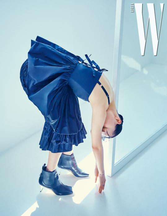 리본 끈 장식 톱, 셔링 디테일 펜슬 스커트는 Molly Gorddard by Hanstyle, 부츠는 Loewe 제품.