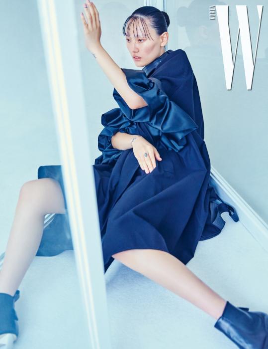 볼륨감 있는 소매 장식이 특징인 코트, 부츠는 Loewe 제품.