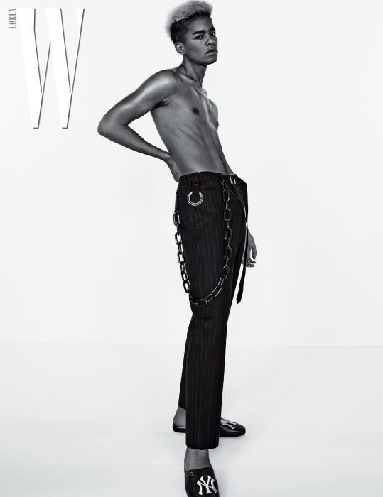 핀 스트라이프 패턴 체인 팬츠는 Maison Mihara Yasuhiro by Boon the Shop, 블로퍼와 머플러는 Gucci 제품.