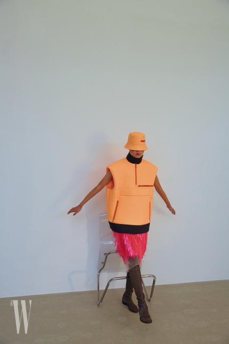 모자와 패딩 베스트, PVC 깃털 장식 스커트는 프라다 제품. 가격 미정. 스웨이드 부츠는 스튜어트 와이츠먼 제품. 80만원대.