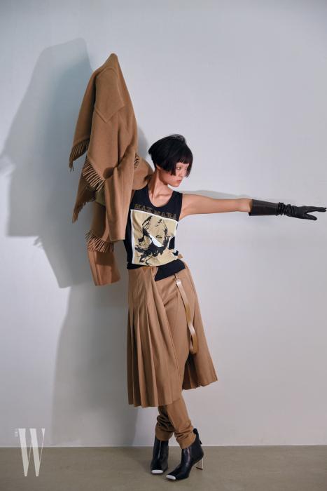 손에 든 캐멀 코트와 허리에 두른 주름 스커트, 팬츠, 프린트 티셔츠, 가죽 장갑, 앵클부츠는 모두 막스마라 제품. 가격 미정.