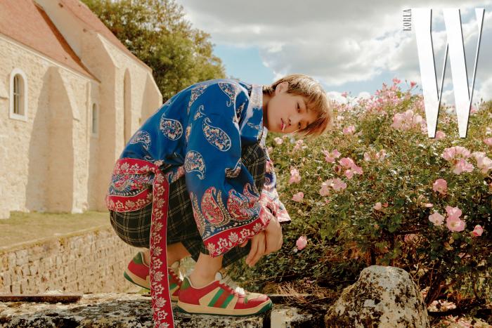 동양적인 아름다움이 느껴지는 페이즐리 패턴 로브와 체크 팬츠, 스니커즈는 모두 Gucci 제품.