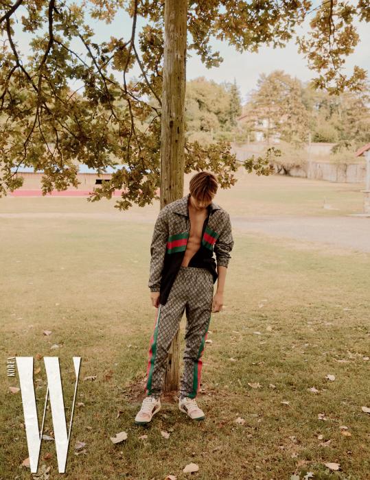 로고 패턴 트레이닝 재킷과 팬츠, 스니커즈는 모두 Gucci 제품.