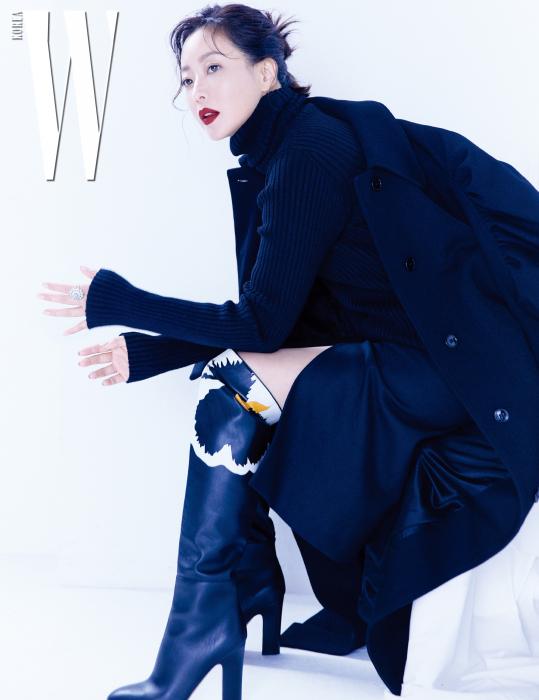 셔링 장식으로 어깨를 강조한 테일러드 코트, 터틀넥 톱, 스커트는 모두 Dries Van Noten, 다이아몬드가 섬세하게 세팅된 해피 다이아몬드 컬렉션 반지는 Chopard, 꽃을 아티스틱하게 표현한 가죽 롱부츠는 Valentino Garavani 제품.