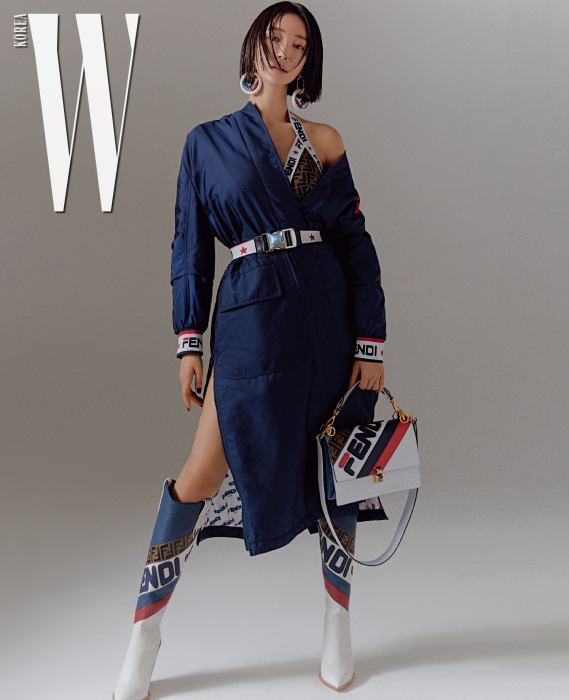 복서가 연상되는 롱 재킷, 로고 장식 이너웨어, 스포티 무드의 벨트, 로고 장식 웨스턴 부츠, 가방, 귀고리는 모두 Fendi 제품.