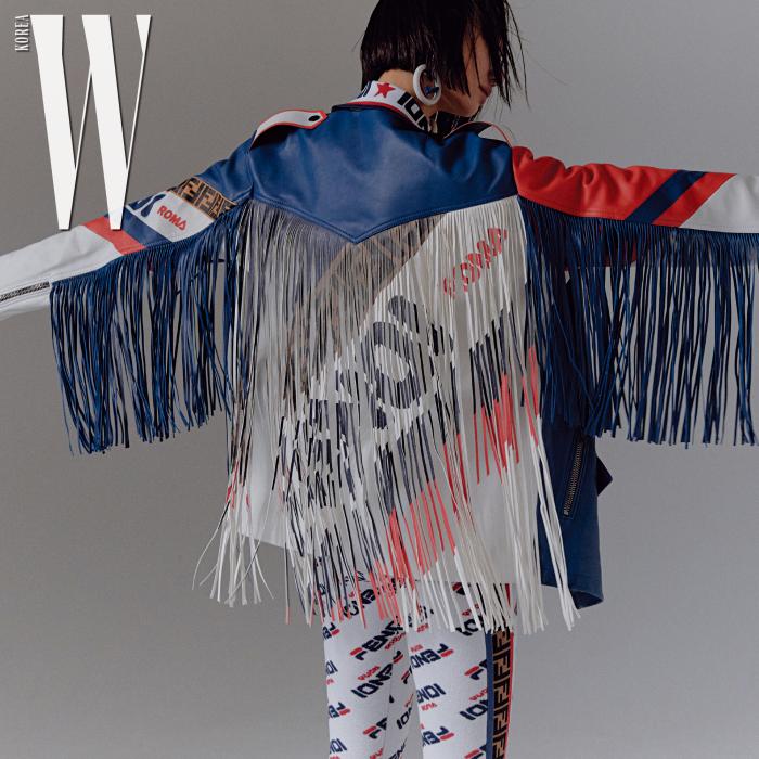 드라마틱한 컬러 블록 프린지 장식 가죽 재킷, 로고 프린트 레깅스, 브라톱, 프린지 장식 가방, 귀고리는 모두 Fendi 제품.