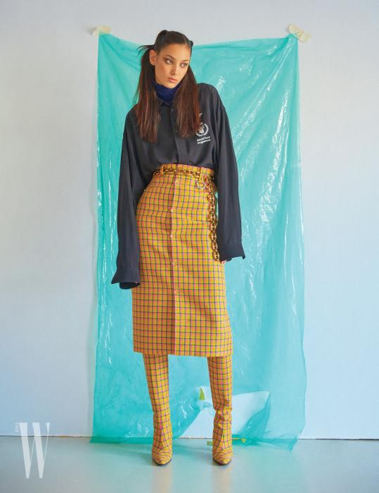 월드 푸드 프로그램 로고 프린트 셔츠, 후디 니트 톱, 스커트, 체인 벨트, 부츠는 모두 Balenciaga 제품.
