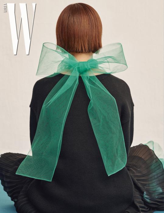 초록색 샤 리본 블라우스는 프라다, 검은색 니트 톱과 시폰 주름 스커트는 폴로 랄프로렌 제품.