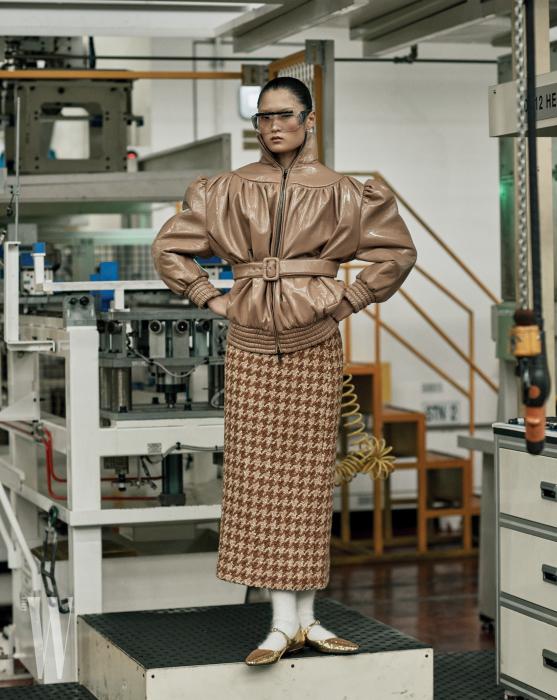 과장된 어깨의 페이턴트 가죽 재킷과 하운즈투스 체크 스커트, 앙고라 소재 양말과 메리제인 슈즈는 모두 Miu Miu 제품.
