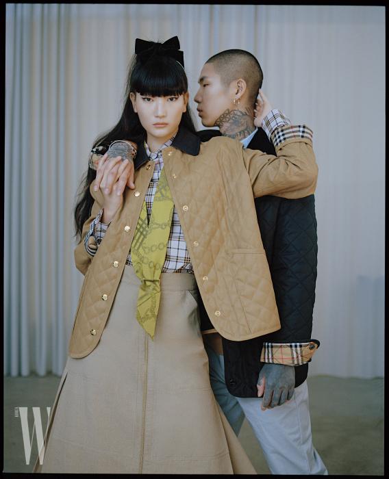 홍나경이 입은 캐멀 퀼티드 재킷과 체크무늬 코튼 셔츠, 베이지색 집업 스커트, 실크 스카프, 당누가 입은 검정 퀼티드 재킷과 옥스퍼드 셔츠, 코튼 팬츠는 모두 Burberry 제품.