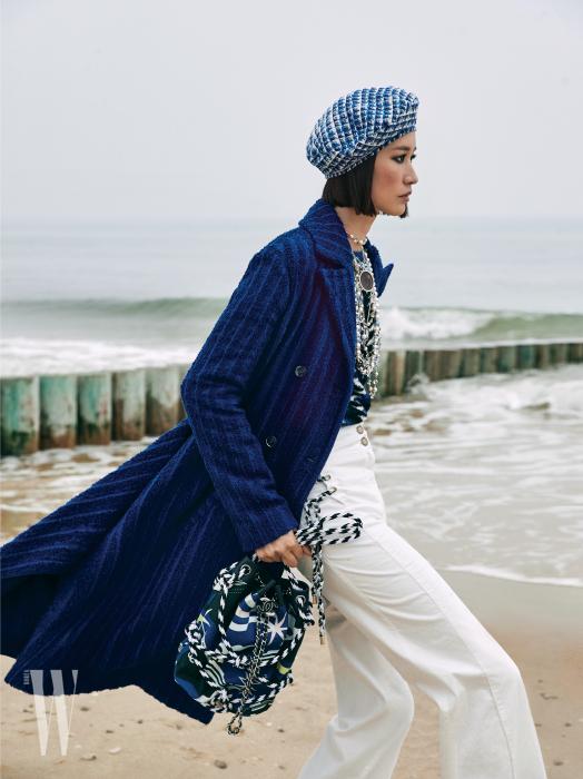 부드러운 니트 톱과 푸른색 코트, 흰색 데님 팬츠, 메탈과 구슬 장식 목걸이와 베레, 밧줄 장식 백은 모두 Chanel 제품.