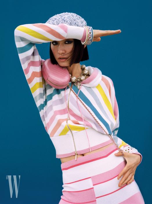 달콤한 색이 조합된 줄무늬 캐시미어 집업 카디건과 스커트, 분홍색 양가죽 핸드백, 메탈과 구슬 장식 목걸이, 컬러풀한 뱅글, 베레는 모두 Chanel 제품.