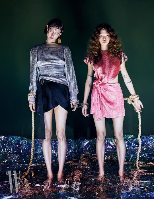 박세라가 착용한 메탈릭 플리츠 톱과 옷핀 장식 쇼츠, 조형적인 귀고리, 손에 감아 연출한 체인 목걸이는 모두 Louis Vuitton 제품. 김아현이 착용한 새틴 드레스는 Louis Vuitton 제품.