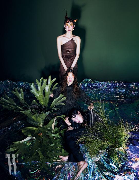 박세라가 착용한 가죽 드레스는 Hermes, 헤드피스는 Q Millinery, 귀고리는 Mzuu 제품. 김아현이 착용한 러플 장식 드레스는 Bottega Veneta 제품. 박경진이 착용한 줄무늬 셔츠와 팬츠는 Saint Laurent by Anthony Vaccarello 제품.