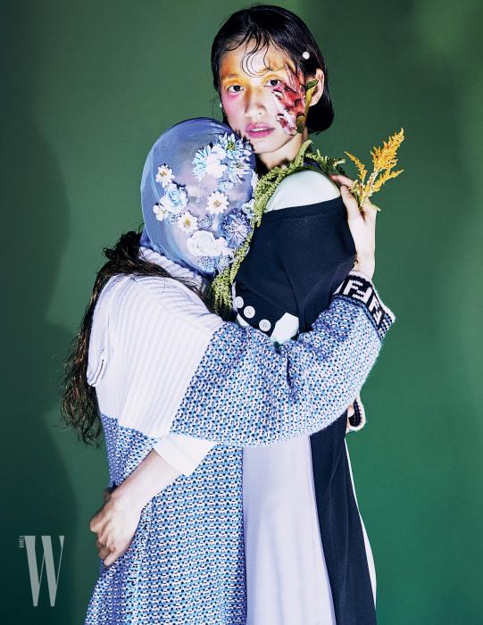 김아현이 착용한 니트 스웨터는 Fendi, 꽃 장식 헤드피스는 Munn 제품. 박세라가 착용한 파스텔 톤 저지 드레스와 검정 카디건은 Marc Jacobs 제품.