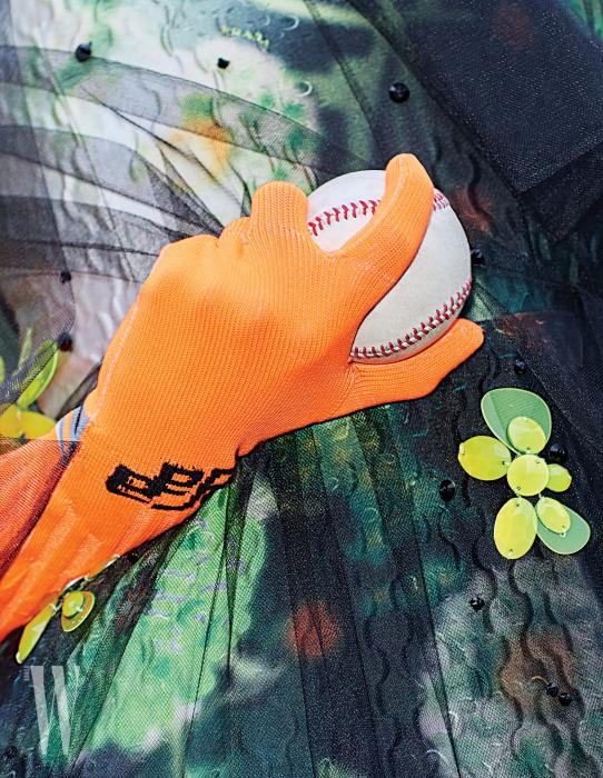 팔꿈치까지 올라오는 오렌지색 니트 장갑과 꽃 모양 장식 드레스는 프라다 제품. 가격 미정.
