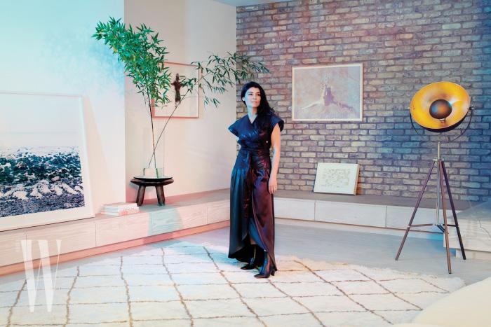 런던에 위치한 자신의 집에서 포즈를 취한 세트 디자이너, 에스 데블린. 데블린이 착용한 톱은 이자벨 마랑, 스커트는 파비아나 필리피 제품.