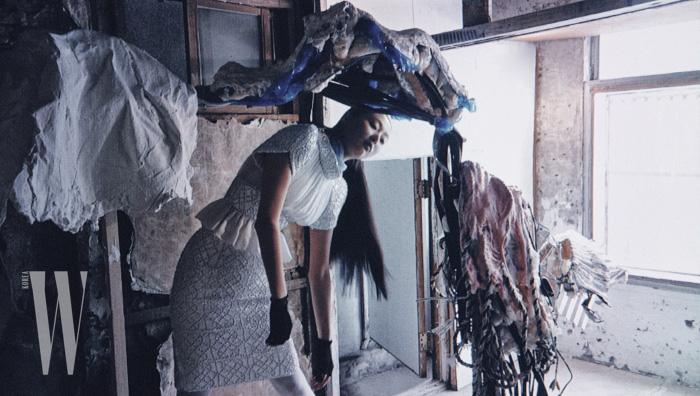 새하얀 비즈 장식 톱과 스커트는 Chanel, 하늘색 스카프는 Prada 제품. 설치 작품은 보안여관의 기획 전시 '내일 없는 내일' 가운데 권용주 작가의 '스트레치 필름 외(2018)'.