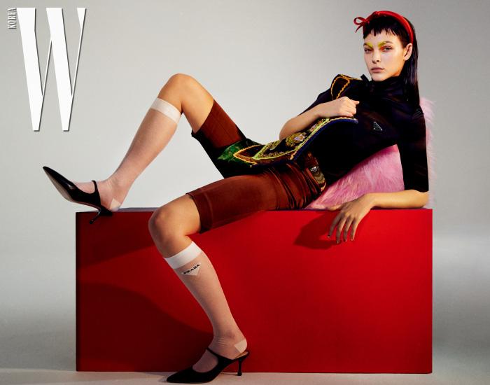 보 장식의 붉은색 새틴 헤어밴드, 검은색 새틴 터틀넥 톱, 갈색 새틴 팬츠, 메탈 장식 벨트, 로고 장식 니삭스, 조형적인 굽의 슈즈는 모두 Prada 제품. 화려한 자수 장식의 알바니아 베스트는 스타일리스트 소장품.