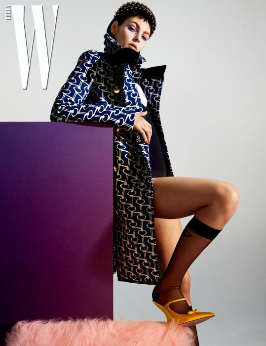 메탈 스터드 장식의 헤어밴드, 그래픽 패턴의 코트, 순백의 셔츠, 검정 보디슈트, 로고 장식 니삭스, 조형적인 굽의 슈즈는 모두 Prada 제품.